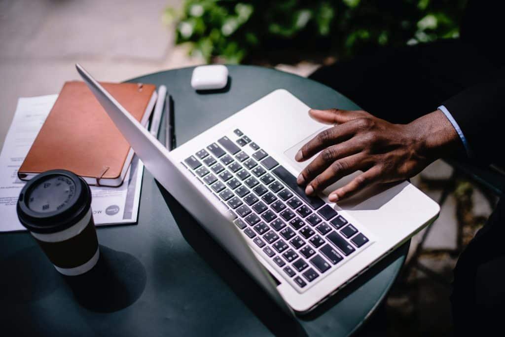 vu du dessus d'un ordinateur posé sur la table d'un café à côté de carnets et d'un café avec la main d'un homme en costume écrivant sur le clavier
